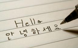 初学者写你好词Annyeonghaseyo的韩语学习者在韩国字符在笔记本 免版税图库摄影