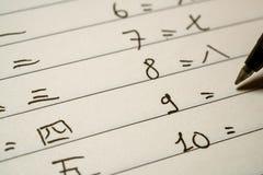 初学者写数字的汉语学习者在汉字在笔记本宏观射击 图库摄影