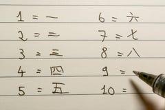 初学者写数字的汉语学习者在汉字特写镜头射击了 免版税库存照片