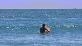 初学者进入海洋的人拿着委员会等待波浪 影视素材