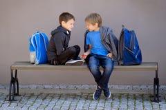 初等教育,学校,友谊概念-有坐,谈话和使用与锭床工人的背包的两个男孩 免版税库存照片