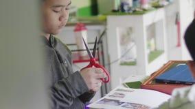 删去剪刀的亚裔儿童男孩在家裱糊 股票视频