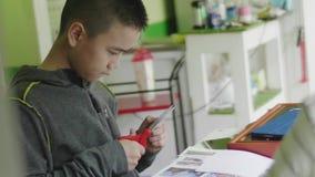 删去剪刀的亚裔儿童男孩在家裱糊 股票录像