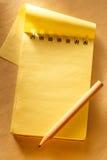 删去与铅笔的开放黄色笔记薄 库存图片