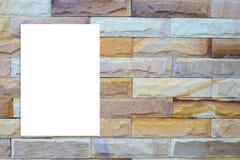 删去垂悬在白色砖墙,模板m上的被折叠的纸海报 免版税库存图片