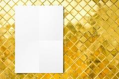 删去垂悬在马赛克金黄瓦片墙壁, Te上的被折叠的纸海报 免版税库存照片