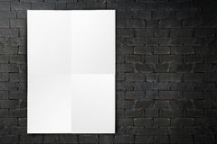 删去垂悬在黑砖墙,模板m上的被折叠的纸海报 库存图片