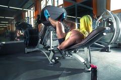 判断健身数炫耀培训妇女年轻人 做在腿的运动人锻炼在健身房在其他人民中 免版税库存图片