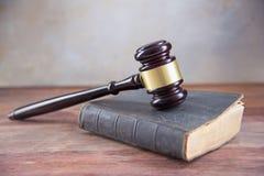 判断在一本旧书的惊堂木在一张土气木桌上,概念为 免版税库存图片