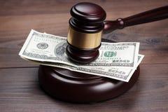 判断在棕色木桌的惊堂木和金钱 免版税库存图片