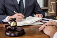 判断有法官标度的惊堂木、女实业家和男性律师或者顾问谈论合同纸在律师事务所在办公室 库存照片