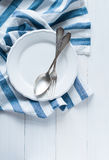 利器、瓷板材和白色亚麻布餐巾 图库摄影