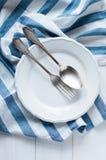 利器、瓷板材和白色亚麻布餐巾 免版税库存图片