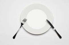 利器和餐馆题目:说谎在一张白色桌上的叉子刀子和白色板材隔绝在演播室顶视图 免版税图库摄影