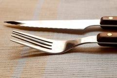 利器的特写镜头图象 与一把刀子的叉子在餐巾 库存照片