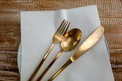 利器集合、黄铜叉子、刀子和匙子在一张木桌上 图库摄影