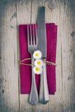 利器-叉子和刀子在紫色餐巾在葡萄酒窗框 免版税库存照片