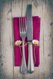 利器-叉子和刀子在紫色餐巾在葡萄酒窗框 库存图片