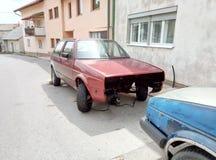 利夫诺/波黑- 2017年6月28日:一条典型的街道的看法在利夫诺 在路旁的被拆卸的汽车 免版税库存照片