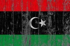 利比亚的旗子在破旧的木纹理背景绘了 库存照片
