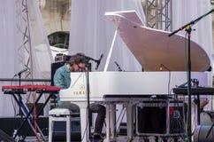 利沃夫州乌克兰2015年6月:阿尔法爵士乐费斯特2015年 音乐家对比弹在阶段爵士节的三重奏带钢琴在市场Squa上 免版税库存图片