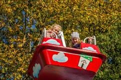 利沃夫州,乌克兰- 2017年10月:小孩,迷人的女孩女朋友在游乐园乘坐在摇摆 免版税库存照片