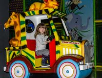 利沃夫州,乌克兰- 2017年11月:小迷人的女孩孩子向乘驾求助在录影的转盘和的戏剧的一个游乐园 免版税图库摄影