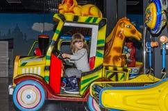 利沃夫州,乌克兰- 2017年11月:小迷人的女孩孩子向乘驾求助在录影的转盘和的戏剧的一个游乐园 免版税库存照片