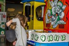 利沃夫州,乌克兰- 2017年11月:小迷人的女孩孩子向乘驾求助在录影的转盘和的戏剧的一个游乐园 免版税库存图片