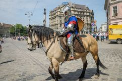 利沃夫州,乌克兰- 2018年5月:骑士坐在狂欢节服装的一匹马在城市的中心乘坐在游行 图库摄影