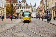 利沃夫州,乌克兰- 2017年11月 一辆现代电车在利沃夫州中心广场  在一个老城市的背景的黄绿电车 免版税库存照片