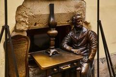 利沃夫州,乌克兰- 2017年11月 对煤气灯的创建者的纪念碑在利沃夫州 一个坐的人的一个古铜色雕象在桌上 免版税库存图片