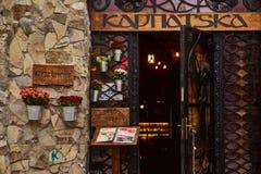 利沃夫州,乌克兰- 2017年11月 对Karpatska餐馆的入口与光的在背景中 金属加工铁门w 免版税库存图片