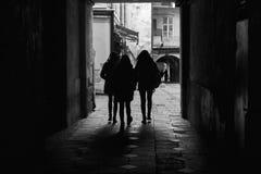 利沃夫州,乌克兰- 2017年11月 走通过一个古城的隧道的人剪影  黑人女孩隐藏人摄影s衬衣白色 免版税库存照片