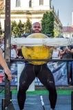 利沃夫州,乌克兰- 2017年8月:一位坚强的运动员爱好健美者举一个巨大的重的石黄色球在大力士比赛 免版税库存照片