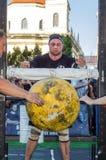 利沃夫州,乌克兰- 2017年8月:一位坚强的运动员爱好健美者举一个巨大的重的石黄色球在大力士比赛 库存照片