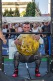 利沃夫州,乌克兰- 2017年8月:一位坚强的运动员爱好健美者举一个巨大的重的石黄色球在大力士比赛 库存图片