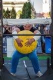 利沃夫州,乌克兰- 2017年8月:一位坚强的运动员爱好健美者举一个巨大的重的石黄色球在大力士比赛 免版税库存图片