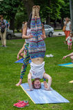 利沃夫州,乌克兰- 2016年6月:在瑜伽期间,教练辅导员教有体育形象的一个年轻迷人的女孩对立场在他的头 免版税图库摄影