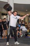 利沃夫州,乌克兰- 2016年11月:坚强的运动员爱好健美者大力士举在观众前面的重的哑铃 库存照片
