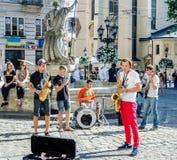 利沃夫州,乌克兰- 2015年7月:弹萨克斯管、鼓和吉他的音乐家以前给一个音乐会在集市广场在利沃夫州 图库摄影