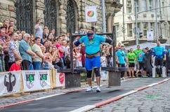 利沃夫州,乌克兰- 2016年6月:运动员有强的身体的爱好健美者大力士有一个极大的金属结构用与标尺o的薄煎饼 免版税库存照片