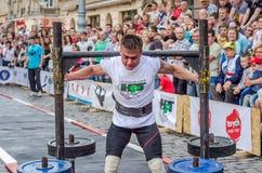 利沃夫州,乌克兰- 2016年6月:运动员有强的身体的爱好健美者大力士有一个极大的金属结构用与标尺o的薄煎饼 库存照片
