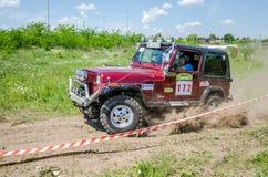 利沃夫州,乌克兰- 2016年5月:驾驶在土路集会的巨大的调整的汽车吉普SUV,培养尘土云彩后边,在spectato中 免版税库存照片