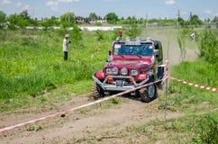 利沃夫州,乌克兰- 2016年5月:驾驶在土路集会的巨大的调整的汽车吉普SUV,培养尘土云彩后边,在spectato中 免版税库存图片
