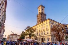 利沃夫州,乌克兰- 2016年9月12日:利沃夫州市和利沃夫州老镇有人的 日落光和利沃夫州香港大会堂 免版税库存图片