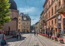 利沃夫州,乌克兰- 2016年9月07日:有地方建筑学和人的利沃夫州市 空的电车方式 库存照片