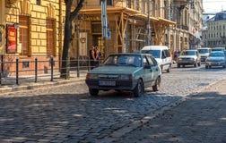 利沃夫州,乌克兰- 2016年9月07日:有地方建筑学和人的利沃夫州市 老LADA车 库存照片