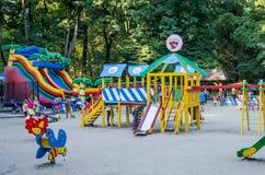 利沃夫州,乌克兰- 2015年8月19日:有摇摆的儿童的游乐场和可膨胀的绷床在儿童游戏的游乐园 免版税库存照片