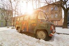 利沃夫州,乌克兰- 2017年2月14日:老嬉皮的样式的葡萄酒减速火箭的被抛弃的汽车被绘的街道画艺术家是残破的在一个  库存图片